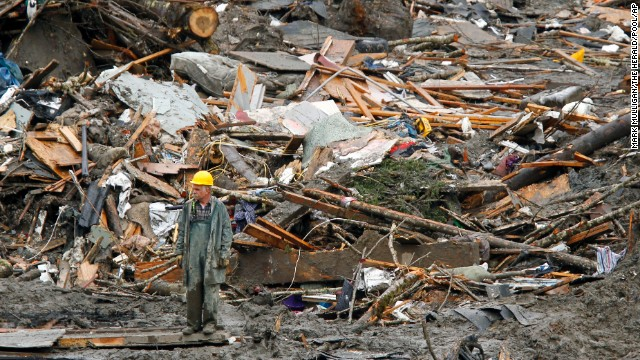 A searcher walks amidst a massive pile of debris at the scene of a deadly mudslide, Thursday, March 27, 2014, in Oso, Wash. The death toll is expected to rise considerably within the next two days as the Snohomish County Medical Examiner's Office catches up with the recovery effort, Snohomish County District 21 Fire Chief Travis Hots said Thursday. (AP Photo/The Herald, Mark Mulligan, Pool)