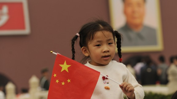 A young girl holds a Chinese flag in front of Tiananmen Gate in Beijing on China National Day on October 1, 2010. Thousands gathered on the square to mark the 61st anniversary of the founding of the People