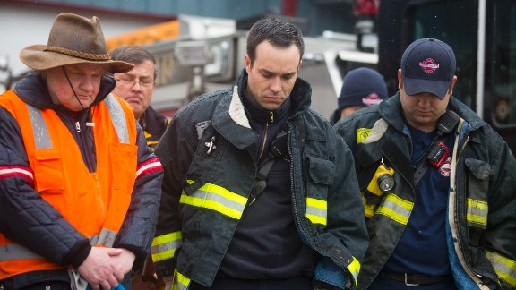 Search-and-rescue personnel attend a moment of silence at the fire house in Darrington.