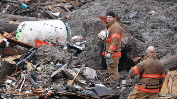 Searchers in Oso pause for a moment of silence on Saturday, March 29. It was observed at 10:37 a.m., exactly one week after the landslide tore through the small community.