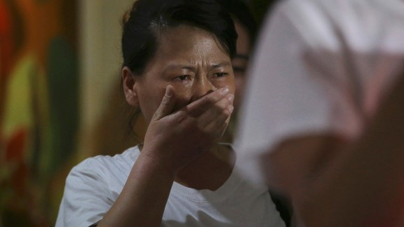 """A newly arrived Chinese relative of passengers on board the missing Malaysia Airlines flight MH370 breaks into tears as they spoke to reporters at a hotel in Subang Jaya, Malaysia, Sunday March 30, 2014. Several dozen Chinese relatives of passengers on Flight 370 arrived in Malaysia Sunday to demand more information about what happened to the airliner that has been missing for more than three weeks, saying there has not been enough information on what happened to their loved ones. Her T-shirt reads: """"Praying that MH370 returns home safely."""" (AP Photo/Aaron Favila)"""