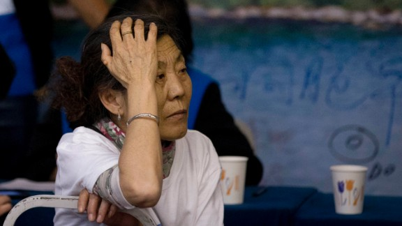 A woman, right, one of the relatives of Chinese passengers aboard the missing Malaysia Airlines flight MH370, sits near volunteers from Malaysia as she attends a briefing by Malaysian officials at a hotel in Beijing Sunday, March 30, 2014. Several dozen Chinese relatives of passengers on Flight 370 demanded Sunday that Malaysia apologize for its handling of the search for the missing plane and for the prime minister's statement saying it crashed into the southern Indian Ocean. (AP Photo/Andy Wong)