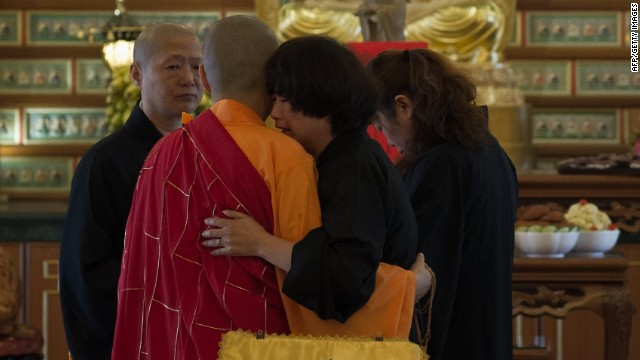 A Buddhist monk comforts a Chinese relative (2nd R) of a passenger from missing Malaysia Airlines flight MH370 after offering prayers at a Buddhist temple in Petaling Jaya on March 31, 2014.