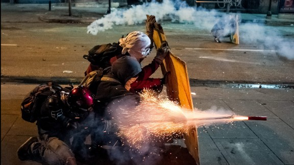 Protesters clash with members of Venezuela's National Police during a protest against President Nicolas Maduro's government on Sunday, March 30, in Caracas.