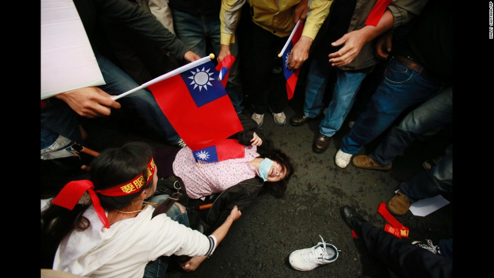 A supporter of the trade pact faints during clashes between protesters and police April 1 in Taipei.