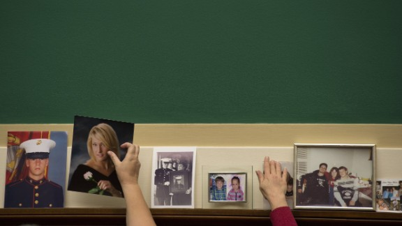 Family members place pictures of their loved ones on the committee wall before the hearing on Capitol Hill.