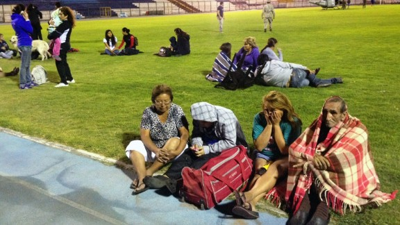 People take refuge at a stadium in Iquique, Chile, after an 8.0-magnitude earthquake struck off the coast of the Latin American country on Tuesday, generating a tsunami.