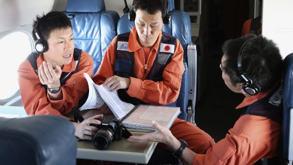 Observers on a Japan Coast Guard Gulfstream aircraft discuss their mission brief before they begin searching for wreckage and debris of missing Malaysia Airlines Flight MH370 in the Southern Indian Ocean on April 1, 2014. Malaysia revealed the full radio communications with the pilots of its missing flight on April 1, but the routine exchanges shed no light on the mystery as an Indian Ocean search for wreckage bore on with no end in sight. AFP PHOTO / POOL / Rob GRIFFITH (Photo credit should read ROB GRIFFITH/AFP/Getty Images)