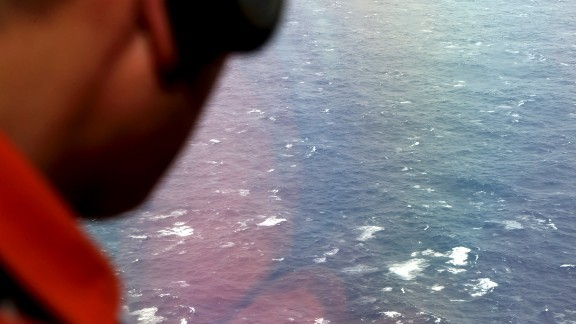 AT SEA - APRIL 01: Kazuhiko Morisawa of the Japan Coast Guard looks out of a window of the Japan Coast Guard Gulfstream aircraft searching for wreckage and debris of missing Malaysia Airlines Flight MH370 in Southern Indian Ocean on April 1, 2014 near Australia. Bad weather and poor visibility caused the search to be called off early with the coast guard plane only completing one of its three 210 nautical mile legs. (Photo by Rob Griffith - Pool via Getty Images)