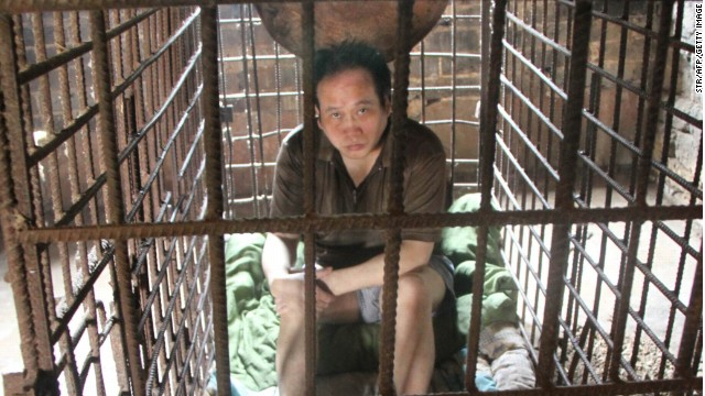 Wu Yuanhong, a mentally ill Chinese man, sits in a cage, which he has been kept in for more than a decade by his family, at their home in Lijiachong village in Jiangxi province.