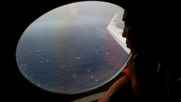 Koji Kubota of the Japan Coast Guard keeps watch through a window of their Gulfstream V aircraft while flying in the search zone for debris from the missing Malaysia Airlines flight MH370 Tuesday, April 1, 2014 off Perth, Australia.