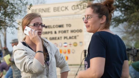 Krystina Cassidy and Dianna Simpson, waiting outside the Bernie Beck Gate at Fort Hood, try to contact their husbands, who are stationed at the post.