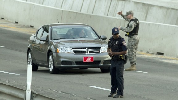 A Bell County Sheriff's Department official stands near a vehicle as cars are checked at the Bernie Beck Gate.
