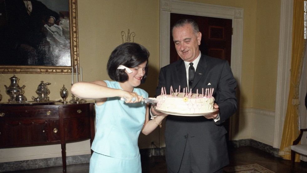 "Luci Baines, with her father helping out, cuts her 17th birthday cake. On that day, LBJ signed the 1964 Civil Rights Act, which she calls ""the best birthday present anyone could ever receive."""