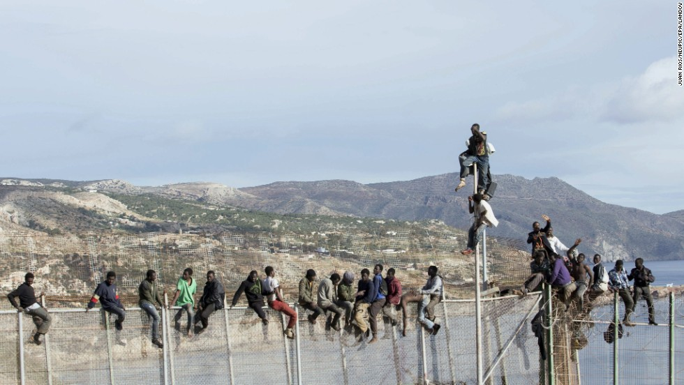 Immigrants from sub-Saharan Africa sit on the top of a fence at the Spanish-Moroccan border as they try to enter Spain on Thursday, April 3.