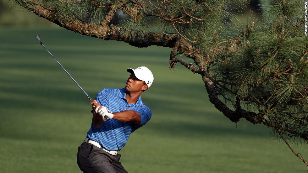 Tiger Woods plays a shot under the Eisenhower Tree at the 2011 Masters, suffering an injury that would cause him to miss four months of the season.