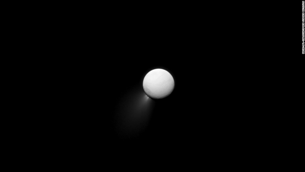 The Saturn-facing side of Enceladus is illuminated by light bouncing off the planet. Plumes of water ice can be seen streaming off the moon's southern pole.