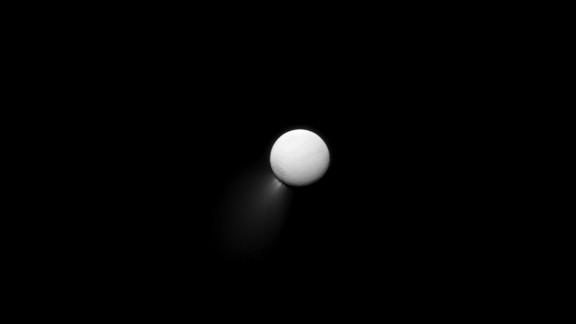 The Saturn-facing side of Enceladus is illuminated by light bouncing off the planet. Plumes of water ice can be seen streaming off the moon