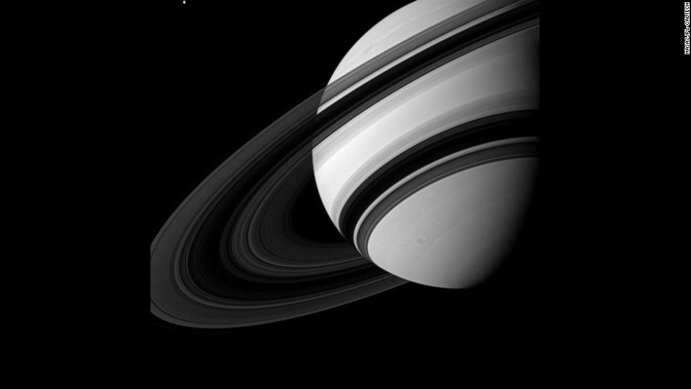 Tethys, top left, is dwarfed by Saturn as it orbits the planet, though scientists think the moon is much larger than Saturn's ring system.