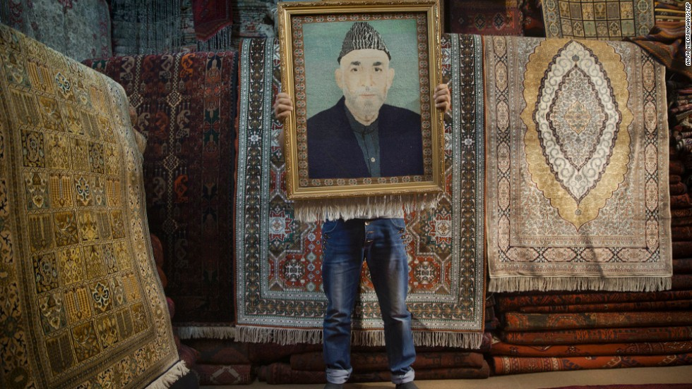 An Afghan carpet seller holds up a framed carpet depicting Afghan President Hamid Karzai on Sunday, March 30.
