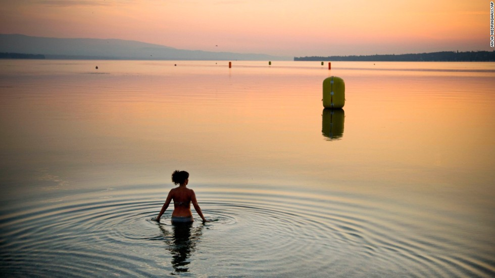 A woman in Geneva, Switzerland, takes a dip in Lake Geneva during a sunrise in July.