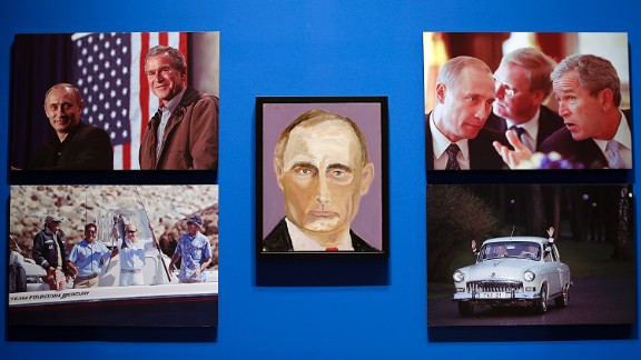 """A portrait of Russian President Vladimir Putin, painted by George W. Bush, is displayed between photographs as part of the library's exhibit """"The Art of Leadership: A President's Personal Diplomacy."""" The exhibit includes more than two dozen never-before-seen portraits by Bush."""