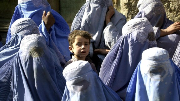 """A young boy stands among a group of veiled women waiting to receive food aid during a U.N. World Food Program distribution in Kabul in November 2001. """"I myself remember the mujahideen"""