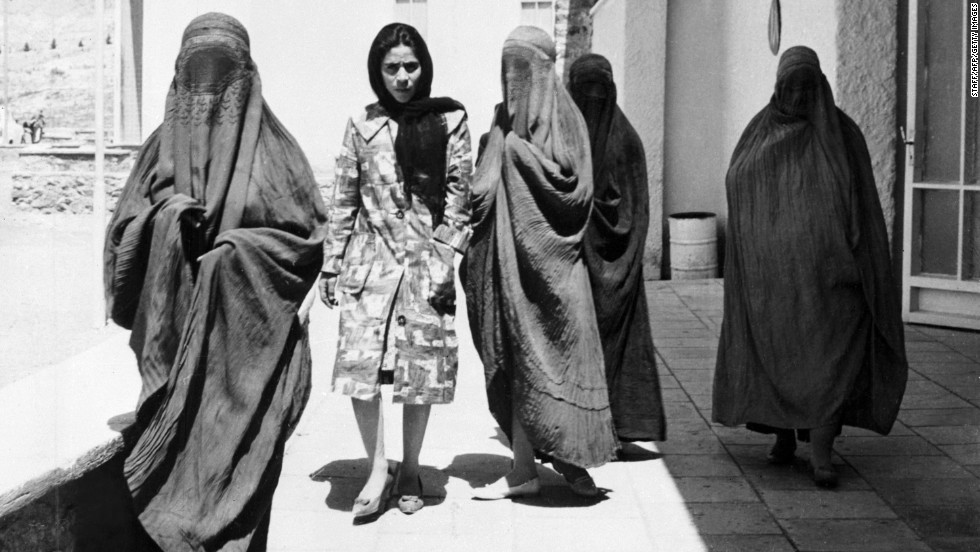 "Taken in 1962, this picture shows Afghan women walking along a street in Kabul. Four of them are wearing burqas, whereas one walks comfortably among them in European-style dress. ""When the mujahideen-led government replaced the Soviets in 1992, new restrictions on dress were formalized,"" says Mosadiq, ""and obviously the Taliban's takeover in 1994 was the final nail in the coffin for any kind of independent dress for both men and women."""