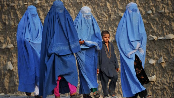 Covered from head to toe, women walk on the outskirts of Jalalabad, accompanied by a liberally-dressed boy, in October 2013. Horia Mosadiq, Amnesty International