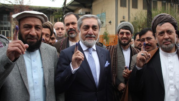 Presidential candidate Dr. Abdullah Abdullah, center, and his running mates Mohammed Mohaqiq, right, and Mohammad Khan, left, show their fingers marked with ink after casting their ballots at a polling station in Kabul.
