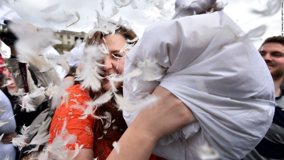 A woman smiles as feathers fly amid the fight at Trafalgar Square in London.