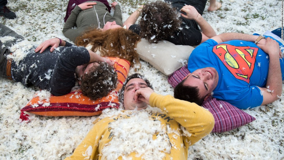 People rest on the ground with their weapons on a bed of feathers during the fight at the Westpark in Berlin.