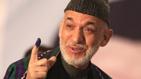 Afghan President Hamid Karzai displays his inked finger after voting.