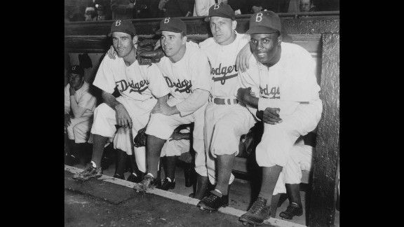 Jackie Robinson, who broke Major League Baseball's color barrier, poses in the dugout with some of his Brooklyn Dodgers teammates during his first game on April 15, 1947.