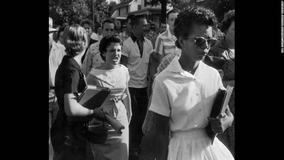 Students of Central High School in Little Rock, Arkansas, shout insults at Elizabeth Eckford as she walks toward the school building on the first day of school in 1957. Schools in Arkansas integrated races after the Supreme Court ruling in Brown v. Board of Education.