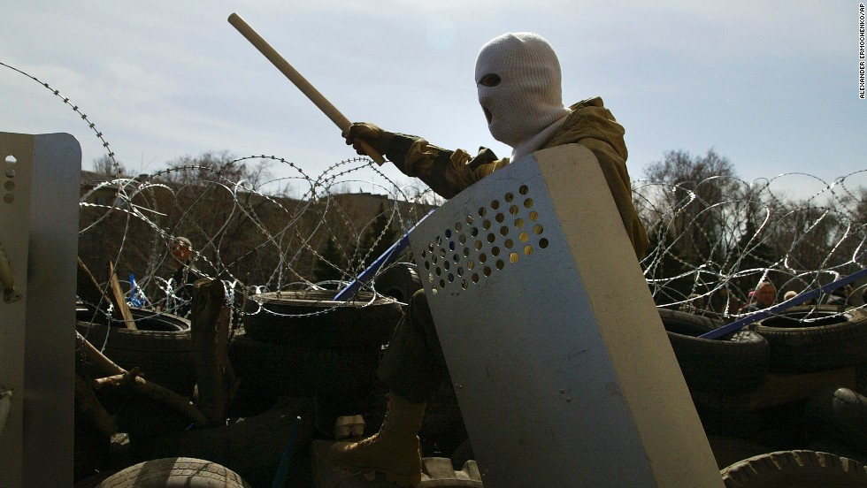 A masked man stands on top of a barricade at the regional administration building in Donetsk on April 7.