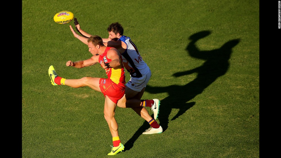 Brendon Matera of the Gold Coast Suns kicks the ball past Pearce Hanley of the Brisbane Lions during an Australian rules football match played Saturday, April 5, in Gold Coast, Australia.