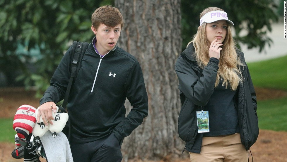 Here he walks with girlfriend Amy during Monday's practice round at Augusta National in Georgia.
