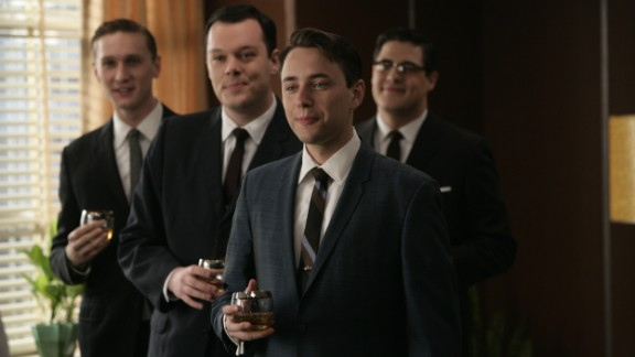 """Wearing dark, formal suits was a nearly century-old tradition by the time """"Mad Men"""" ad men donned identical looks -- with highballs -- at the Sterling Cooper agency in 1960. Their suits' slim silhouettes came from returning WWII soldiers' athletic figures, said University of Notre Dame history professor and author Linda Przybyszewski. Suits narrowed in the shoulders, torso and legs to fit the new physique."""