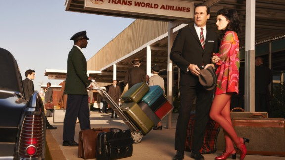 """Don and Megan Draper show up to the airport in fashionably bright colors in this promotional photo for the seventh season. While researching 1960s fashion, Przybyszewski was surprised to find that women's dresses in the late 1960s could be even shorter than Megan's. The money spent on tights and pantyhose worn with these dresses was """"mind-boggling,"""" she said."""