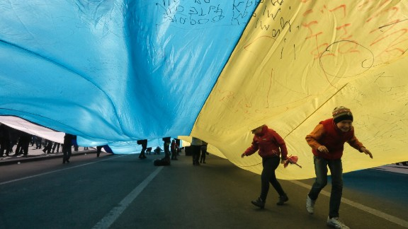 Ukrainian kids play under a huge yellow-and-blue Ukrainian national flag at a rally in Kiev's Independent square, Ukraine, Saturday, April 5, 2014.