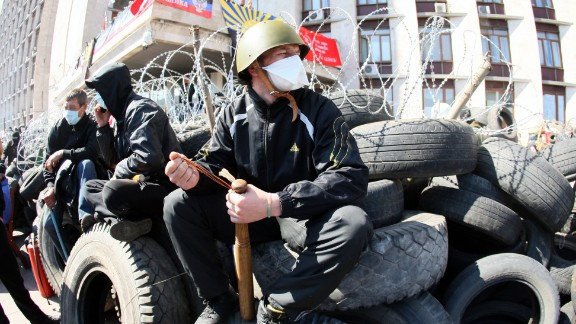 "A pro-Russian militant holding a bat guards a barricade in front of the Donetsk regional administration building on April 8, 2014. Ukraine mounted a counteroffensive on April 8 by vowing to treat the separatists as ""terrorists"" and making 70 arrests in a nighttime security sweep, while hundreds of militants remained holed inside the Donetsk administration building a day after proclaiming the creation of an independent ""people"