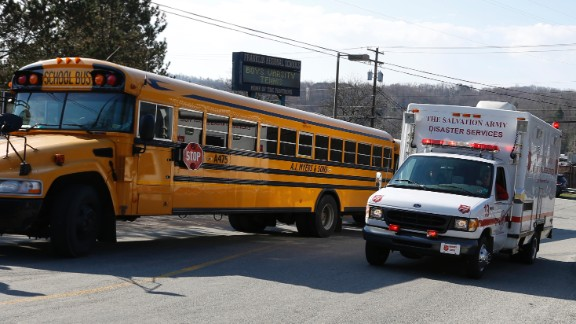 A Salvation Army disaster services vehicle drives past a school bus and onto the campus on April 9.