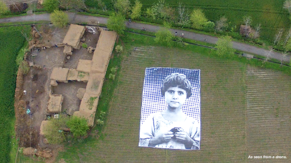 In a field in Pakistan, the face of a little girl stares into the sky, her gaze a haunting rebuke to the drones that killed her family in 2010. The name and location of the child is unknown.