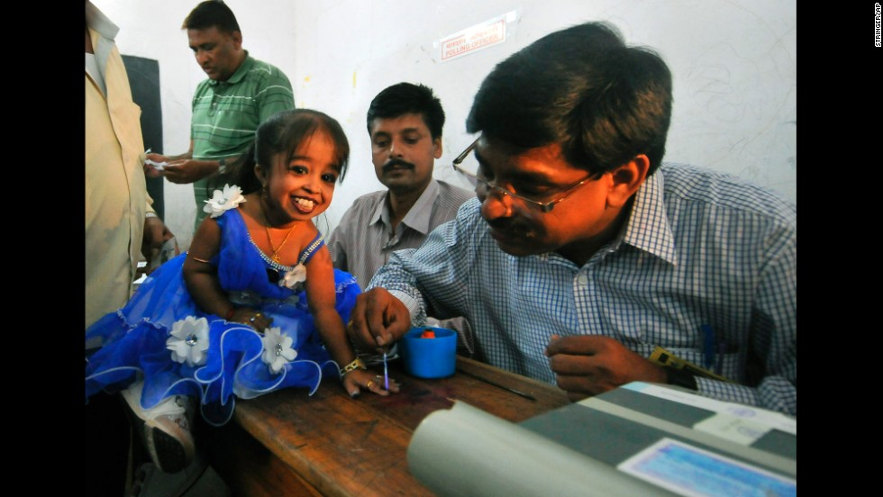 Jyoti Amge, a first-time voter and the world's shortest woman according to Guinness World Records, gets her finger marked with ink after voting in Nagpur, India, on April 10.