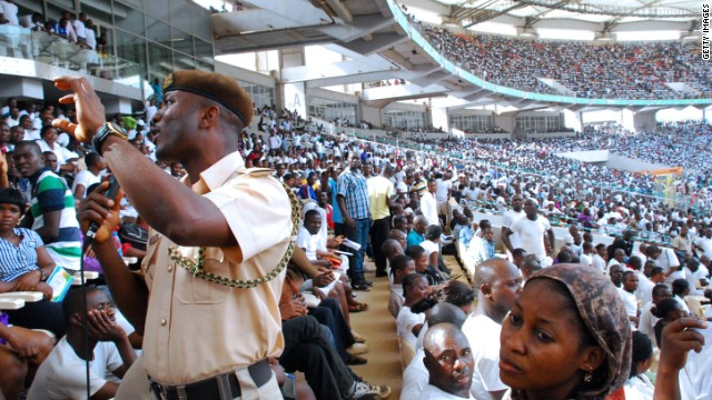 A security agent speaks to job-seekers gathered in Abuja National Stadium to apply for work at the Nigerian immigration department on March 15, 2014.