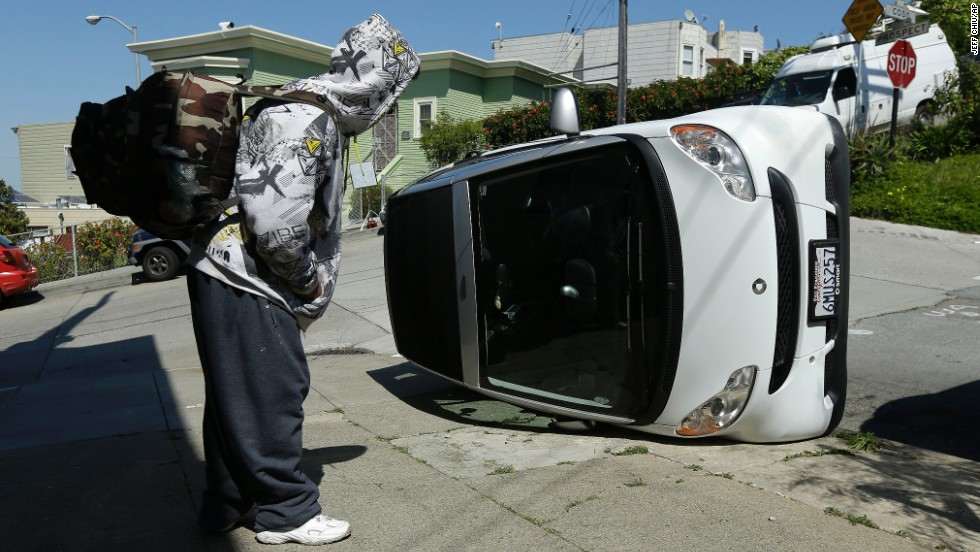 "A man looks at a tipped-over Smart car Monday, April 7, in San Francisco. Police said four Smart cars <a href=""http://www.cnn.com/2014/04/08/us/smart-car-flipping-san-francisco/"">were flipped over</a> in an apparent early morning vandalism spree."
