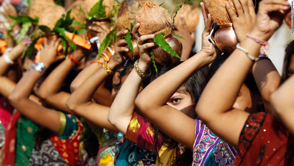 Women in Vadodara, India, hold copper pots and coconuts over their heads on Wednesday, April 9, to give a traditional welcome to Narendra Modi, a candidate running for prime minister.