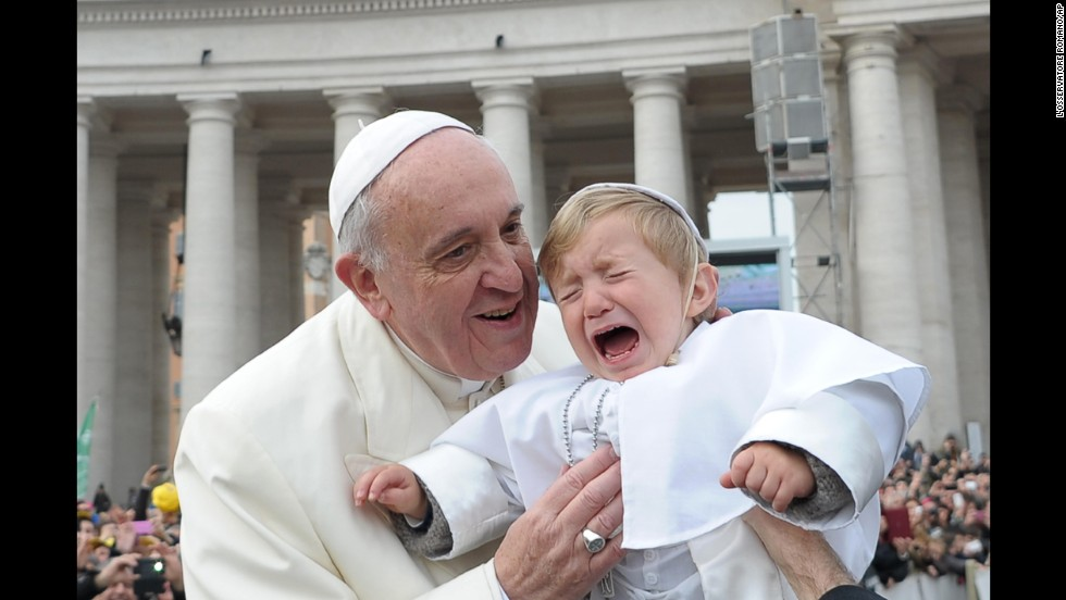 Daniele De Sanctis, a 19-month-old dressed as the pope, is handed to Francis as the pontiff is driven through the crowd in St. Peter's Square in February 2014.