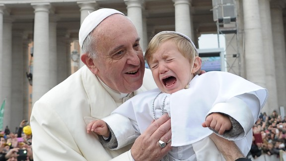 Daniele De Sanctis, a 19-month-old dressed as the pope, is handed to Francis as the pontiff is driven through the crowd in St. Peter